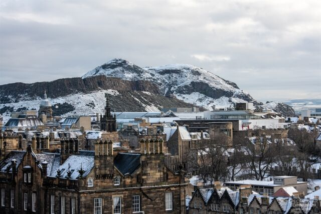 A snowy Arthur's Seat and Salisbury Crags towering over the city - Edinburgh looks especially nice with a light dusting of snow on the rooftops! Perhaps you can make out the National Museum of Scotland and Old College?  _____  Tom 🙂